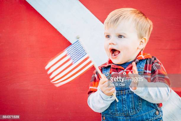 Caucasian boy waving American flag outside barn