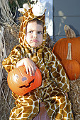 Caucasian Boy Wearing A Giraffe Costume And Frowning On Halloween