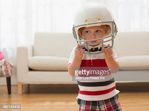 Caucasian boy wearing football helmet