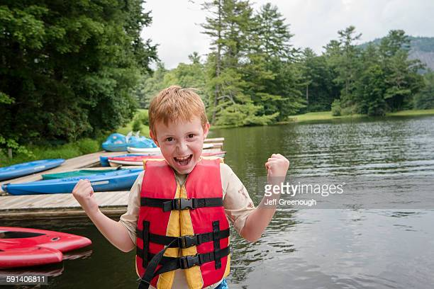 Caucasian boy wearing lifejacket by lake