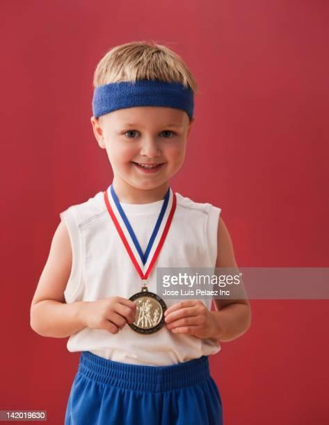 Caucasian boy wearing sports medal