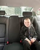 Caucasian boy wearing suit in back seat of car