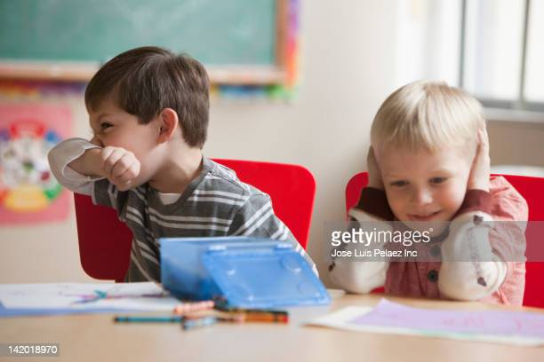 Caucasian boy wiping his nose in classroom