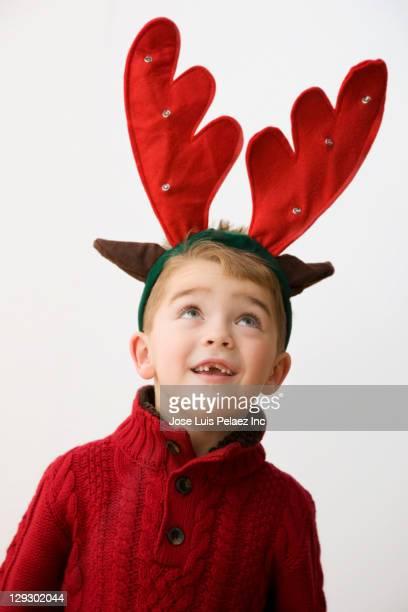 Caucasian boy with reindeer antlers headband on his head