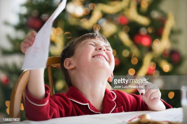 Caucasian boy writing Christmas letter to Santa
