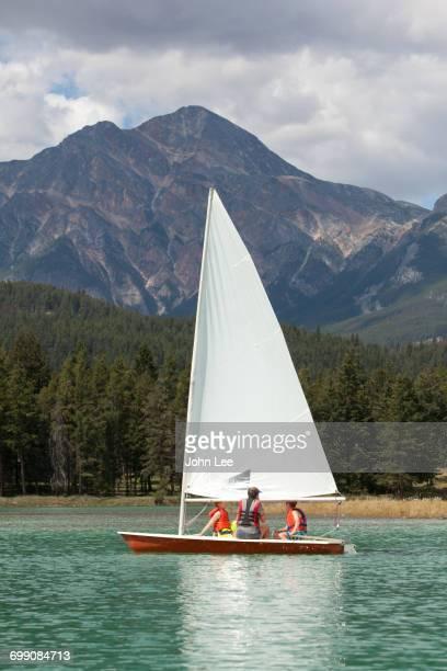 Caucasian boys and girl sailing on lake