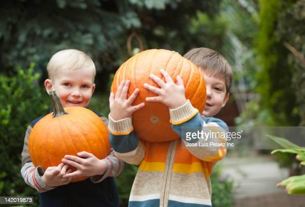 Caucasian boys carrying pumpkins