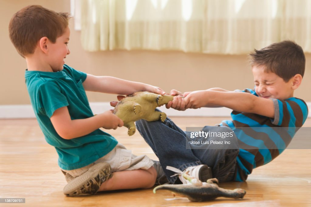 Caucasian boys fighting over dinosaurs