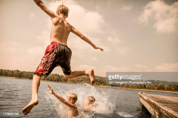 Caucasian boys jumping off wooden dock