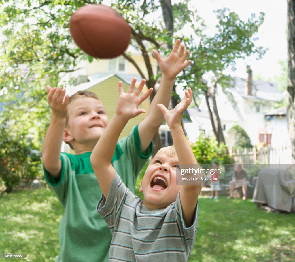 Caucasian boys playing football in backyard