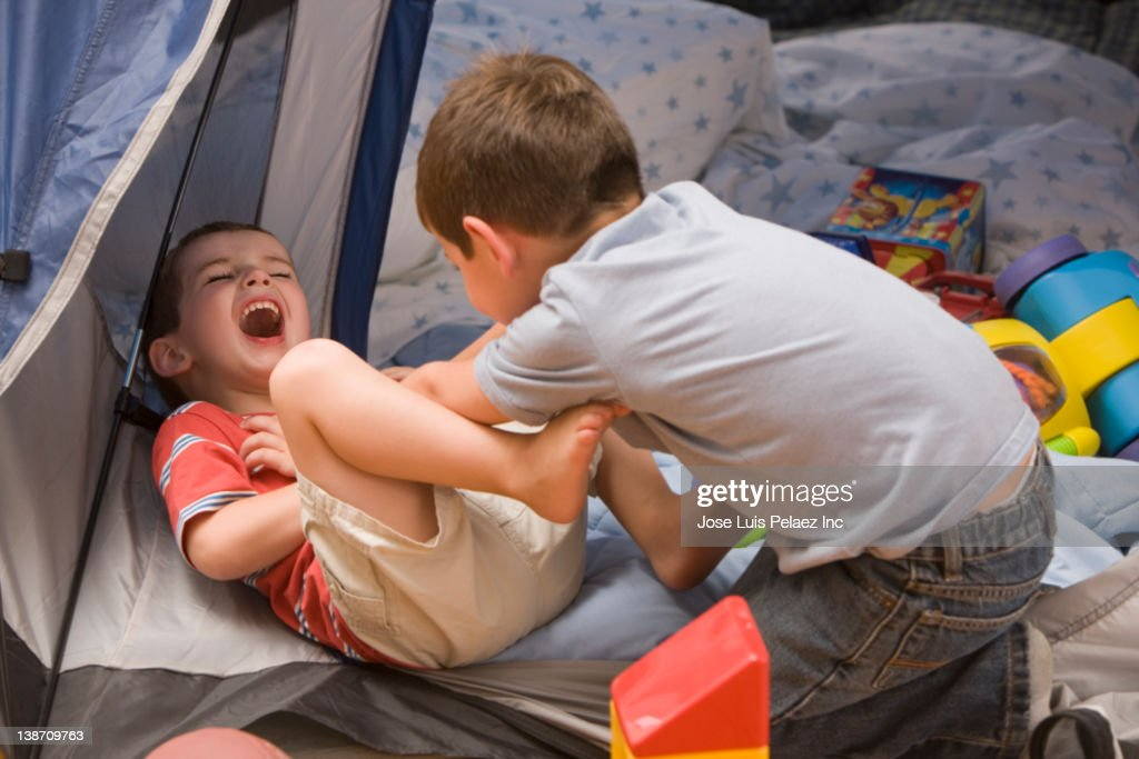 Caucasian boys playing in tent : Stock Photo
