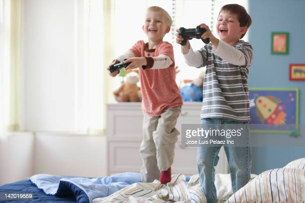 Caucasian boys playing video game