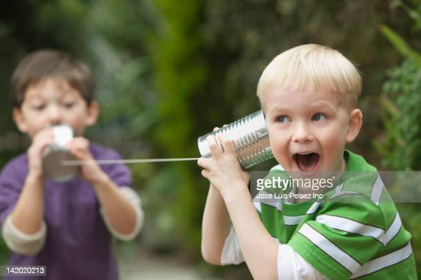 Caucasian boys playing with tin can telephone