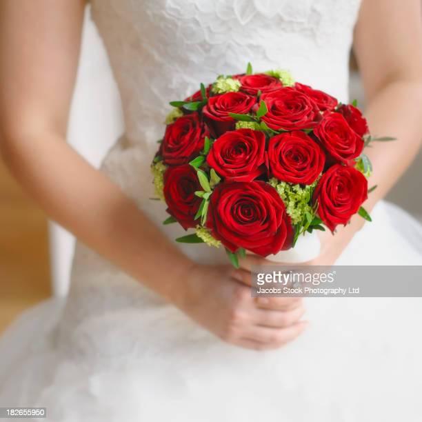 Caucasian bride holding bouquet of red grand prix roses