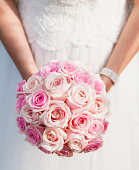Caucasian bride holding bouquet of sweet avalanche roses