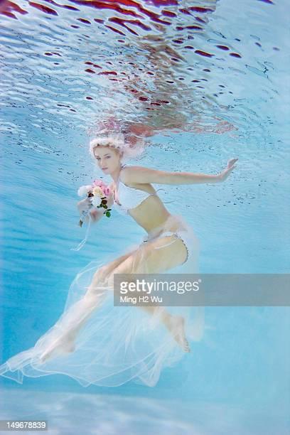 Caucasian bride in bikini swimming under water