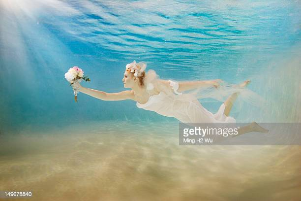 Caucasian bride in wedding dress swimming under water