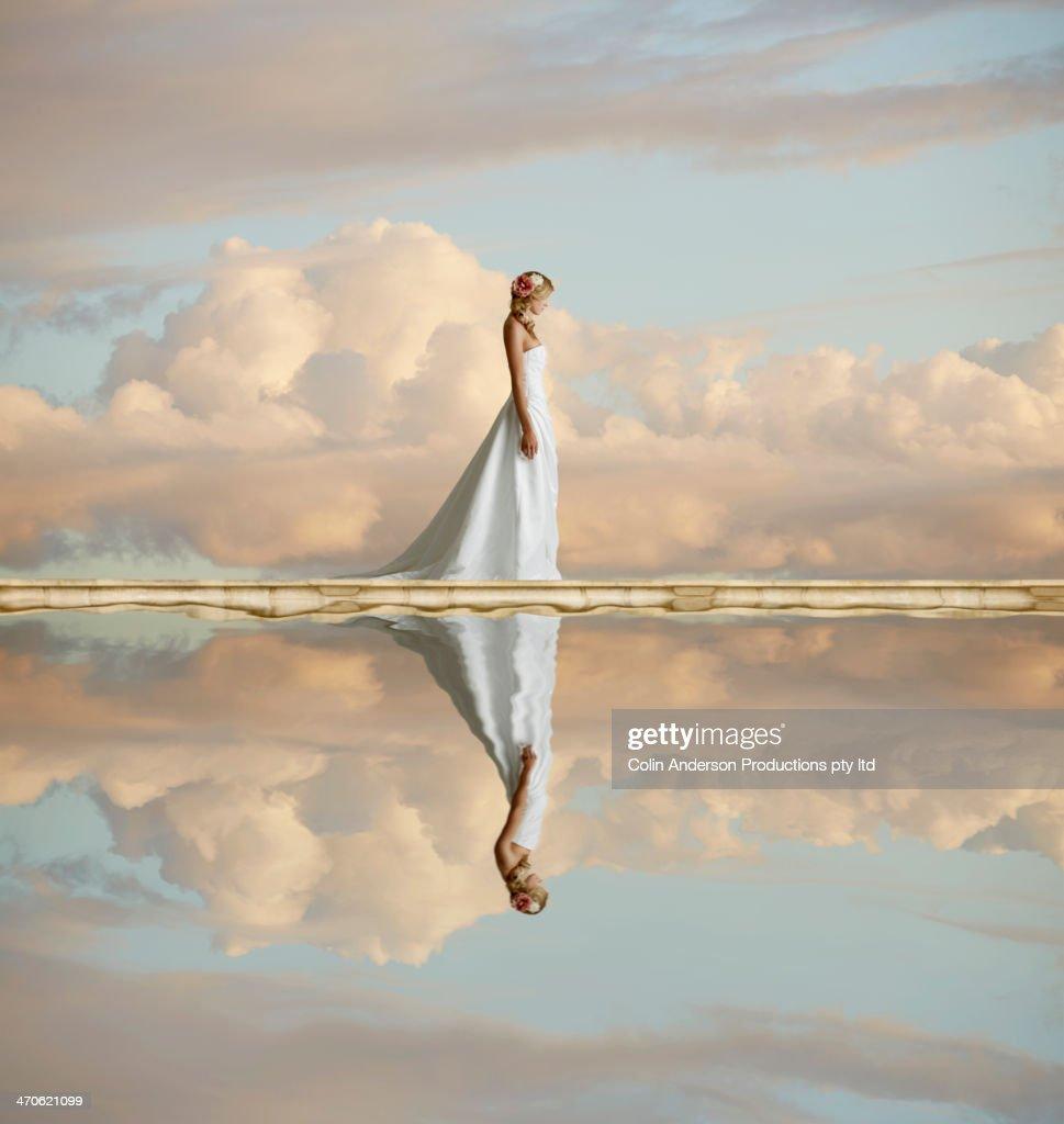 Caucasian bride reflected in still lake