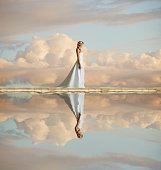 Caucasian bride reflected in still lake