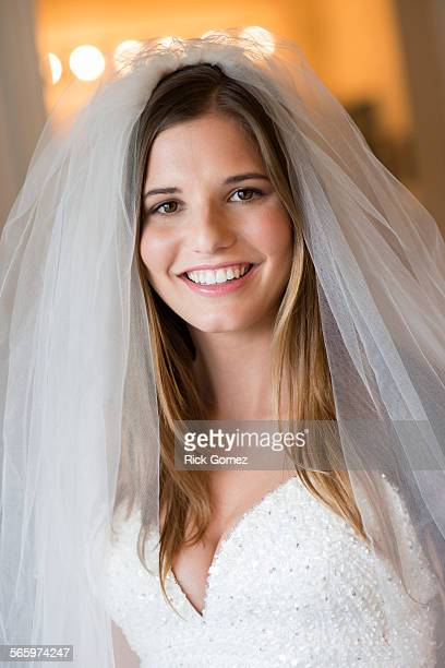 Caucasian bride smiling in wedding gown and veil