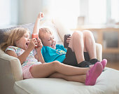 Caucasian brother and sister cheering with cell phones on sofa