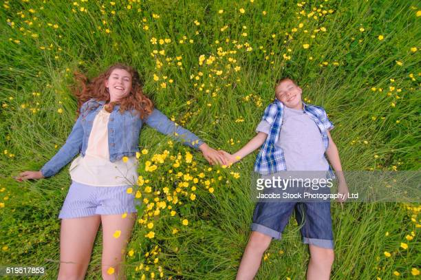 Caucasian brother and sister holding hands in field of flowers