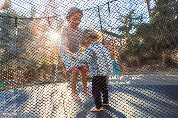 Caucasian brother and sister jumping on trampoline
