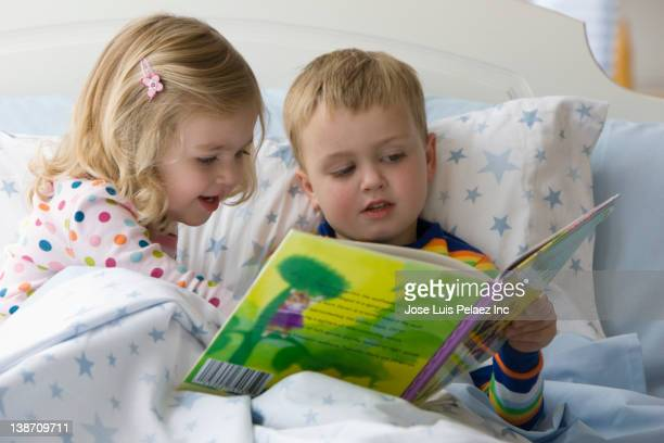 Caucasian brother and sister reading book in bed