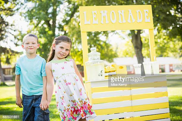 Caucasian brother and sister smiling at lemonade stand
