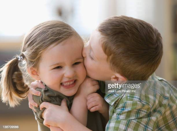 Caucasian brother kissing sister