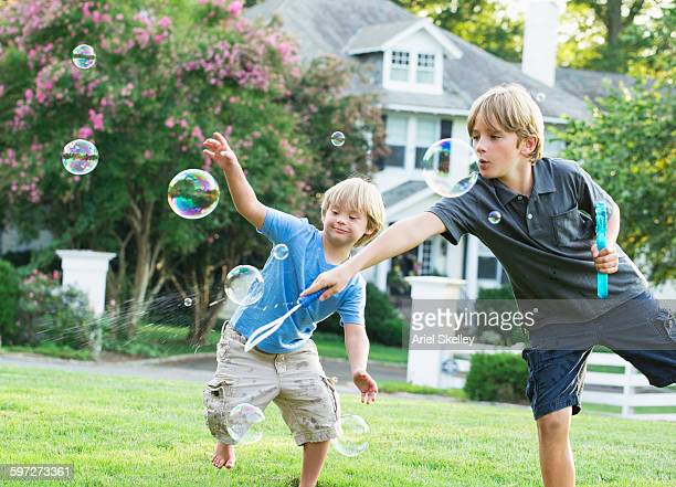 Caucasian brothers playing with bubbles
