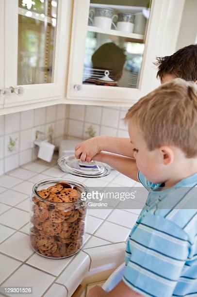 Caucasian brothers sneaking cookies in kitchen