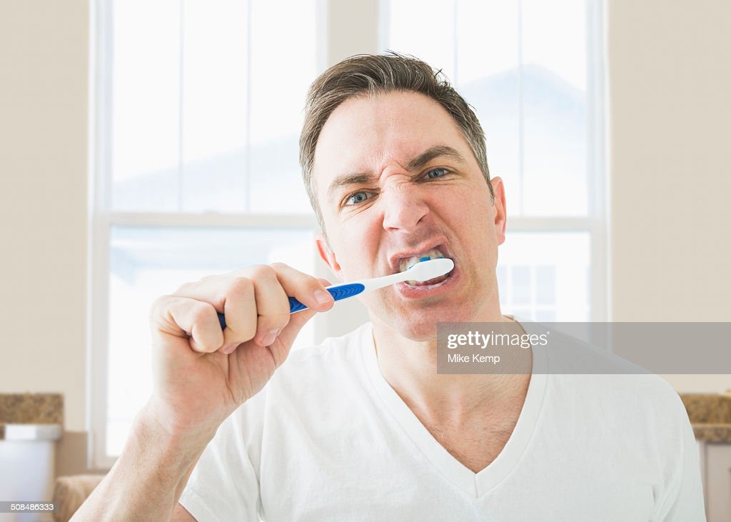 Caucasian brushing his teeth in bathroom