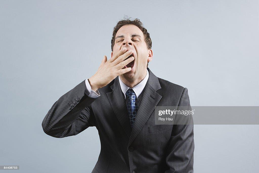 Caucasian business man yawning : Stock Photo
