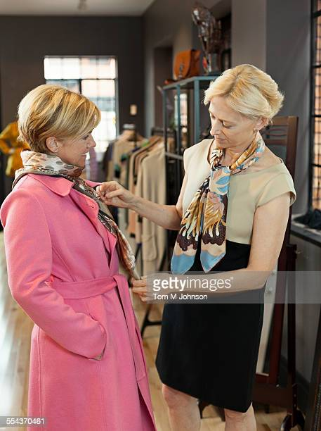 Caucasian business owner helping customer shop in clothing store