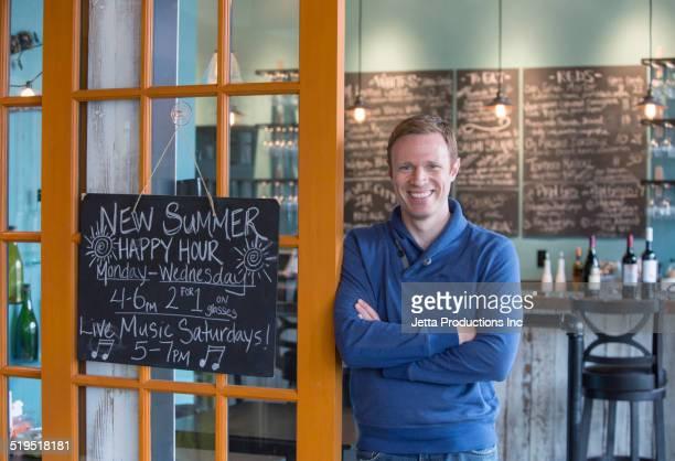 Caucasian business owner smiling in wine bar