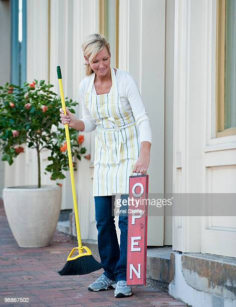 Caucasian business owner sweeping sidewalk