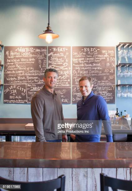 Caucasian business partners smiling in wine bar