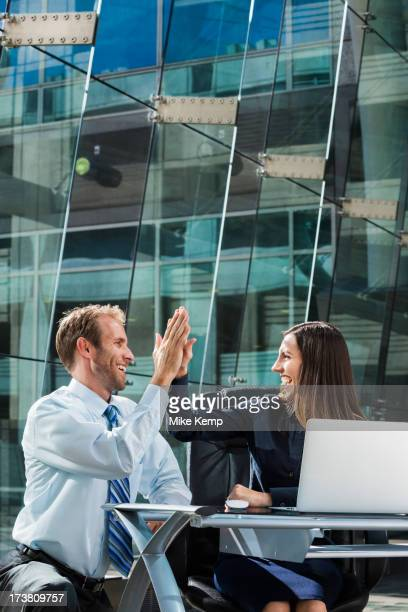 Caucasian business people high fiving at desk