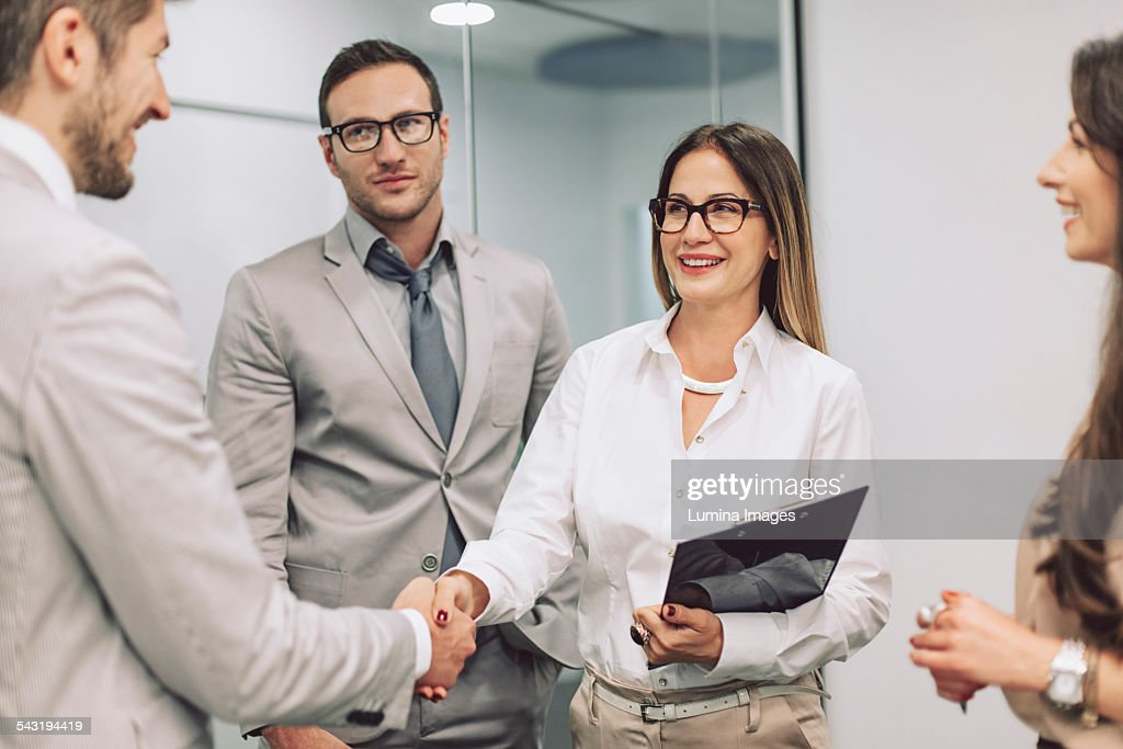 Caucasian business people shaking hands in office
