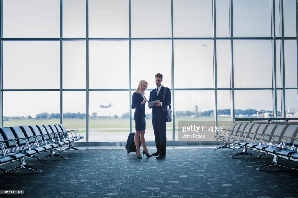 Caucasian business people standing in airport : Stock Photo