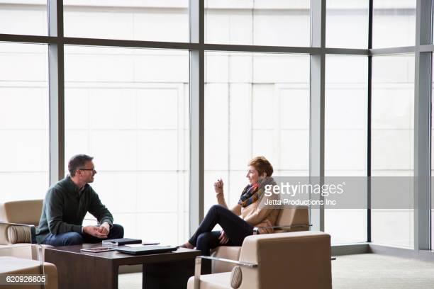Caucasian business people talking in office lounge