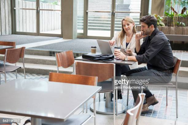 Caucasian business people using laptop at table