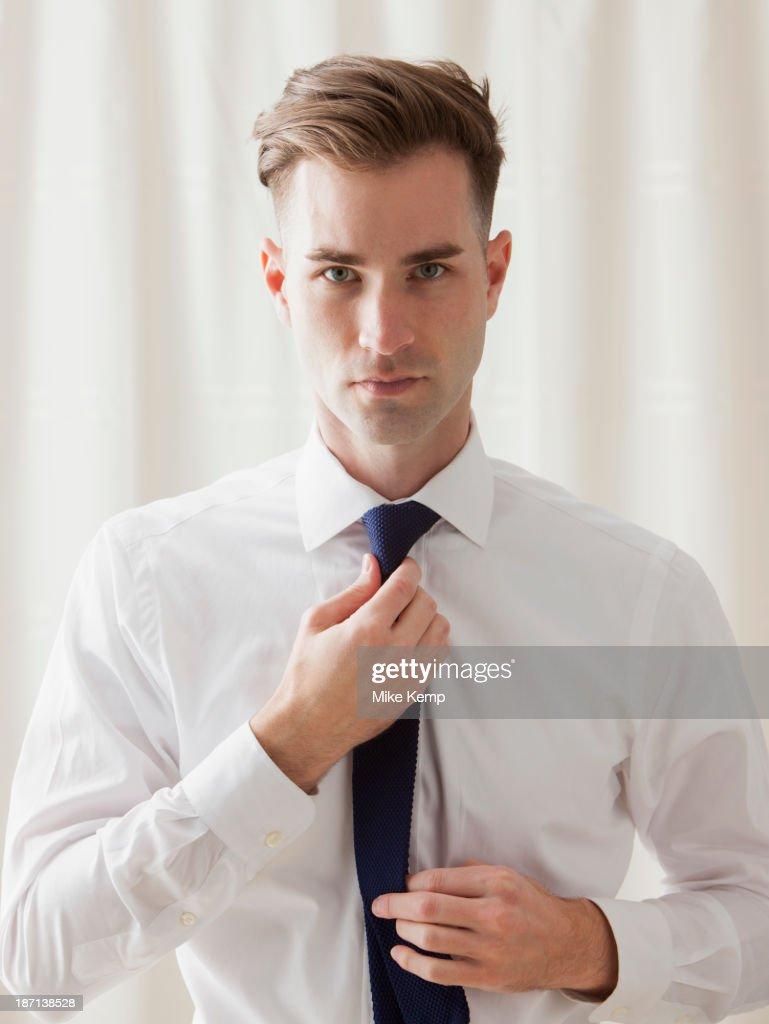 Caucasian businessman adjusting his tie