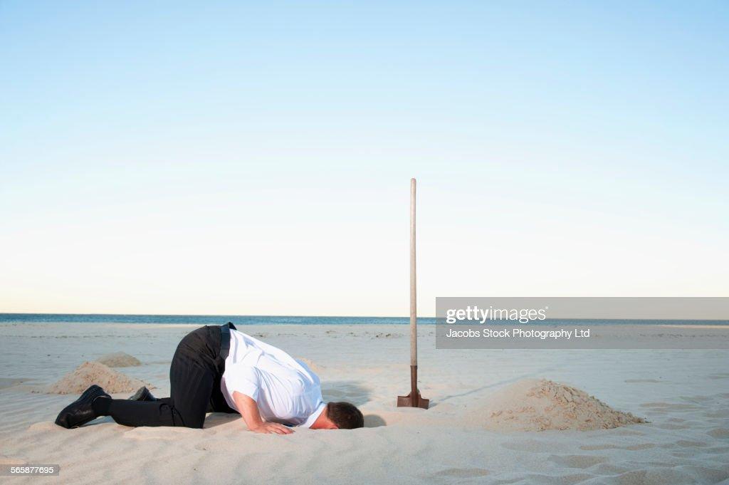 Caucasian businessman burying head in sand