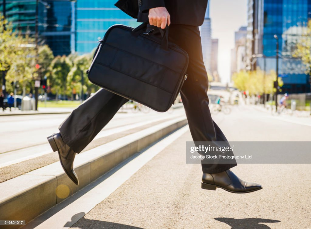 Caucasian businessman carrying briefcase across city street
