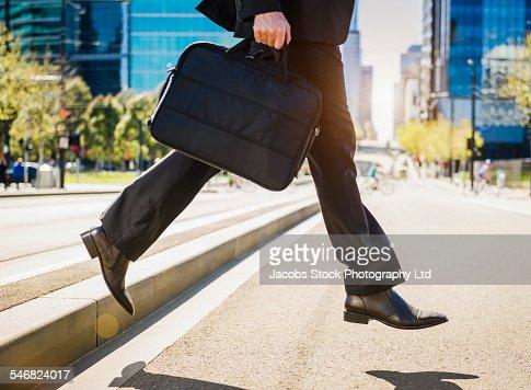 Caucasian businessman carrying briefcase across city street