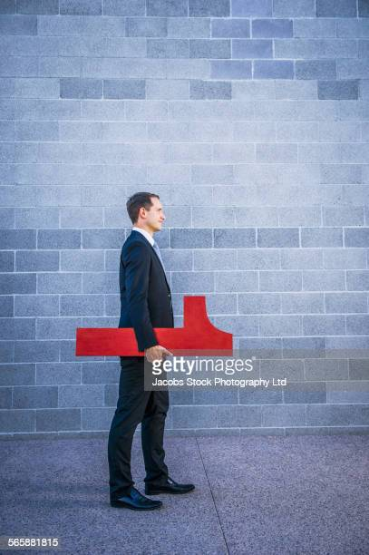 Caucasian businessman carrying number one near brick wall