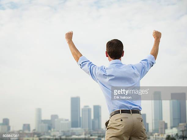 Caucasian businessman cheering on urban rooftop