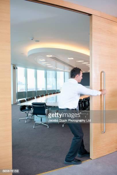 Caucasian businessman closing sliding door to conference room